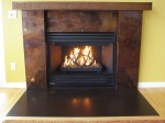 Fireplace-remodel: Micro-hammer embossed copper mantle with patina, copper with patina surround, steel with patina hearth. Custom burner with fireglass and steel sculpture.